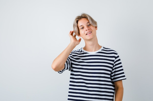 Teen boy toucher ses cheveux en t-shirt et à la charmante, vue de face.