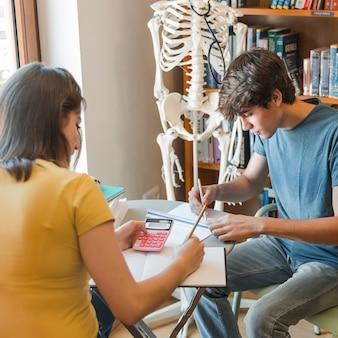 Teen couple étudiant dans la bibliothèque