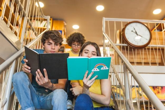 Teen couple étudiant sur les marches de la bibliothèque