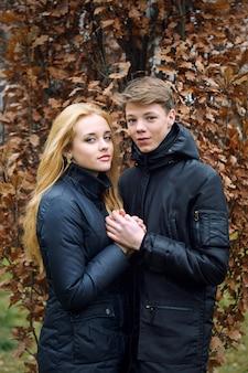 Teen couple se tenant sur le fond des feuilles d'automne