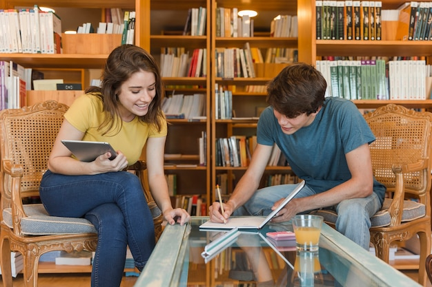 Teen couple avec tablette étudie dans la bibliothèque