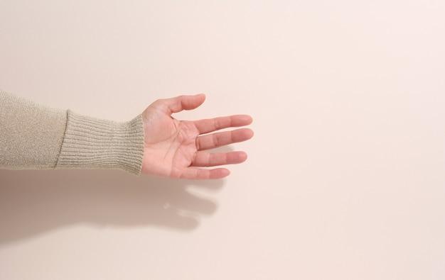 Teen femelle main pour tenir quelque chose sur un fond beige. publicité et promotion des produits