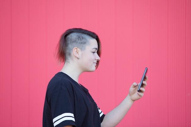 Teen femme androgyne se connectant à internet sur un mur rose