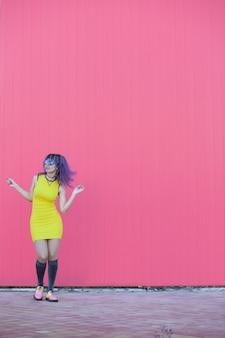 Teen femme aux cheveux afro violet danse avec une robe jaune cool sur un mur rose