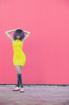 Teen femme aux cheveux afro violet avec une robe jaune cool sur un mur rose