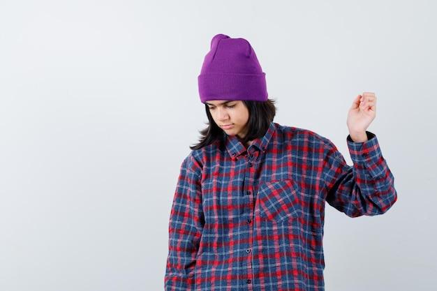 Teen femme en chemise à carreaux et bonnet gesticulant isolé