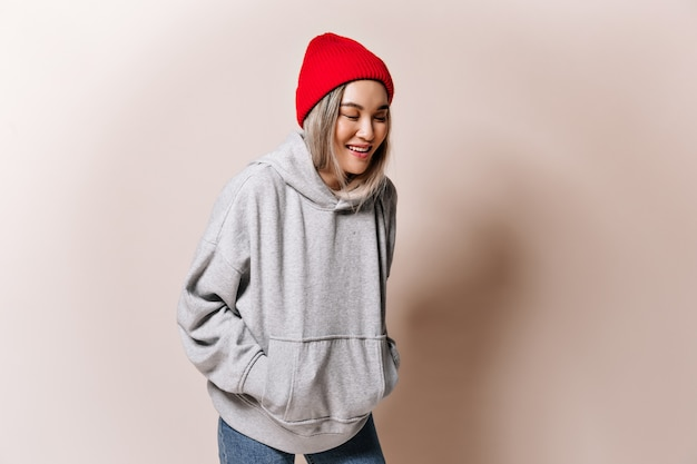 Teen femme en sweat-shirt et chapeau rit sur mur beige