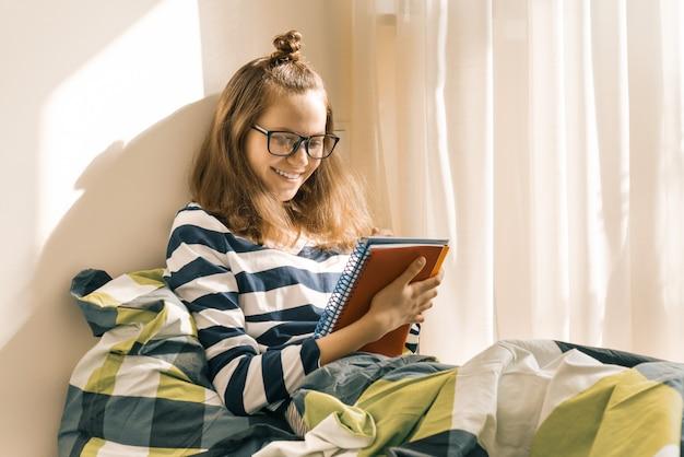 Teen fille étudiant à la maison assis dans son lit