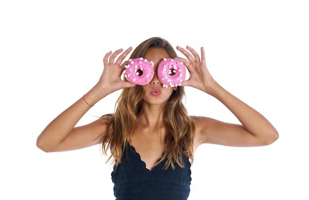 Teen fille tenant des lunettes de beignets sur ses yeux