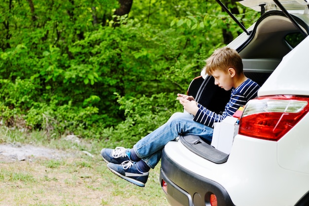 Teen garçon assis dans la voiture avec téléphone
