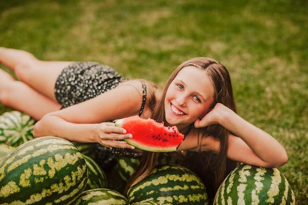 Teen girl assis sur un tas de pastèques et tenant une tranche d'un dans un jardin