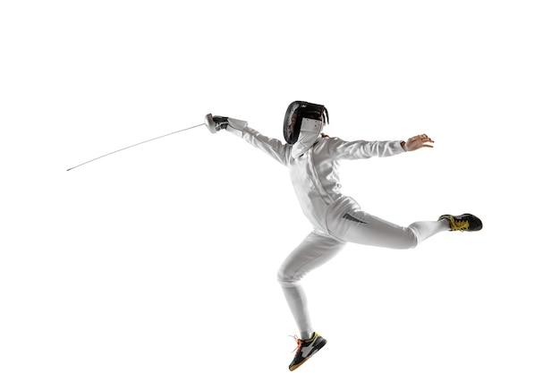 Teen girl en costume d'escrime avec épée à la main isolé sur fond de studio blanc. jeune mannequin caucasien pratiquant et s'entraînant en mouvement, action. espace de copie. sport, jeunesse, mode de vie sain.