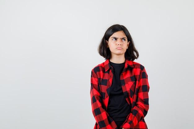 Teen girl à l'écart tout en courbant les lèvres en t-shirt, chemise à carreaux et l'air déçu. vue de face.