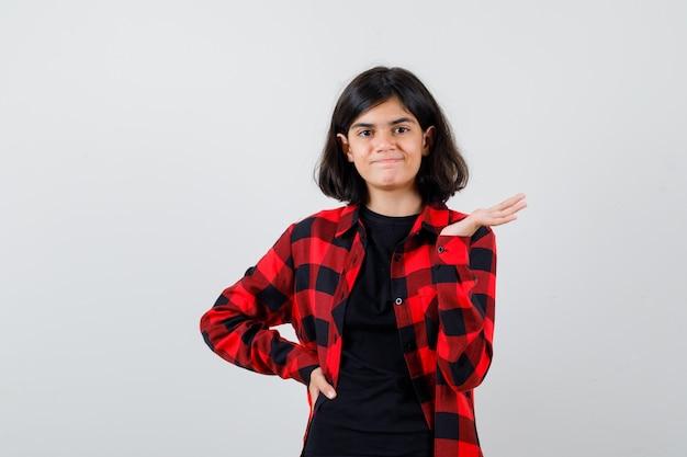 Teen girl faisant un geste de bienvenue en t-shirt, chemise à carreaux et l'air heureux, vue de face.