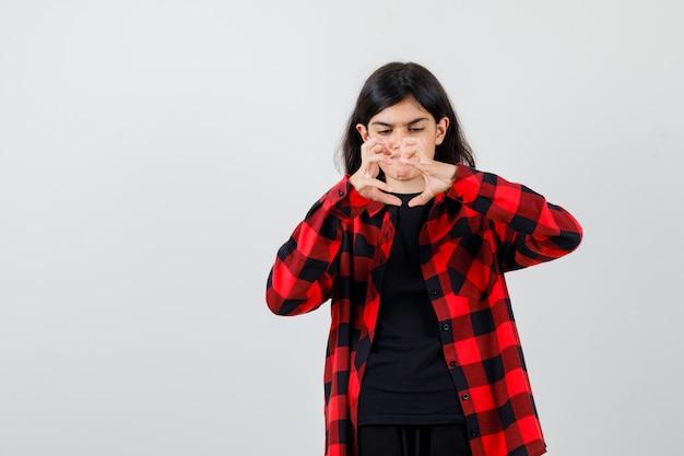 Teen girl faisant semblant d'attraper quelque chose en t-shirt, chemise à carreaux et l'air sérieux, vue de face.