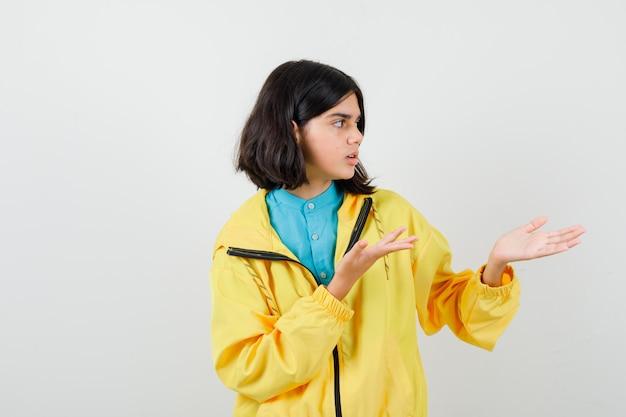 Teen girl faisant semblant de montrer quelque chose en veste jaune et à la perplexité , vue de face.