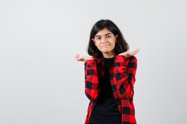 Teen girl faisant semblant de tenir quelque chose en t-shirt, chemise à carreaux et l'air heureux, vue de face.