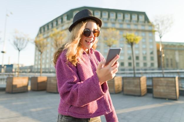 Teen girl hipster en chapeau et lunettes avec téléphone portable