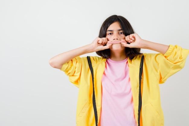 Teen girl holding et étirant ses lèvres en survêtement jaune, t-shirt et l'air sérieux, vue de face.