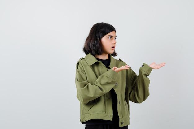 Teen girl in army green jacket faisant semblant de montrer quelque chose, regardant de côté et se demandant , vue de face.