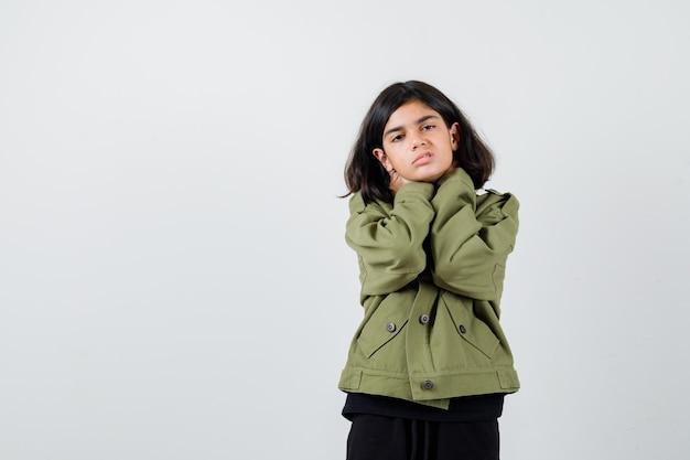 Teen girl in army green jacket souffrant de douleurs au cou et ayant l'air en détresse, vue de face.