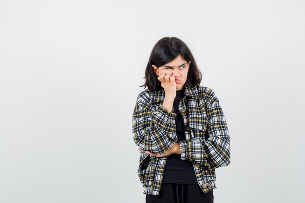 Teen girl in casual shirt en appuyant la main sur la joue, en détournant les yeux et en ayant l'air ennuyé, vue de face.