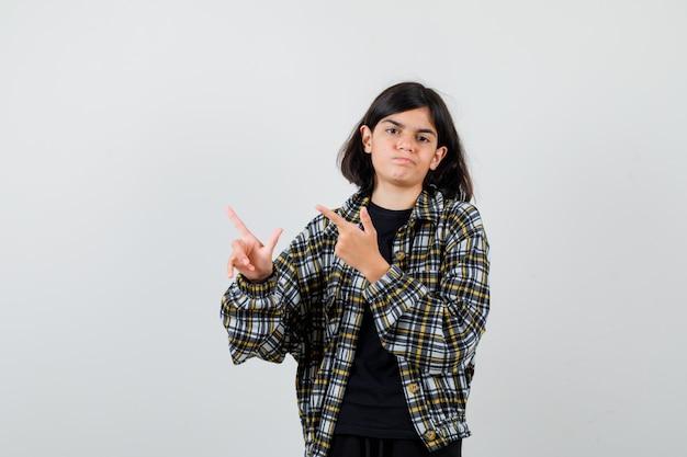Teen girl in casual shirt pointant vers le coin supérieur gauche et l'air déçu , vue de face.
