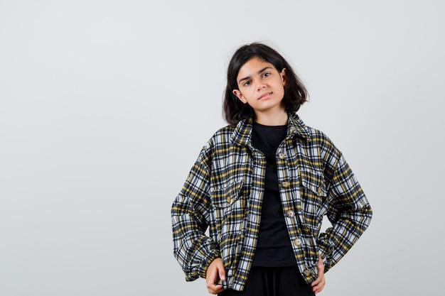 Teen girl in casual shirt posing tout en gardant les mains sur la hanche et à la félicité, vue de face.