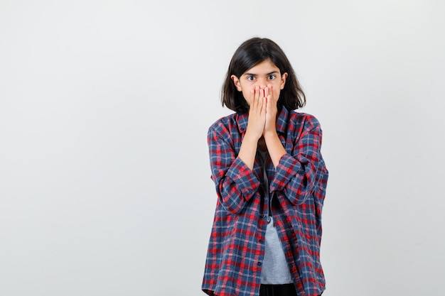 Teen girl in checkered shirt couvrant la bouche avec les mains et à la peur , vue de face.