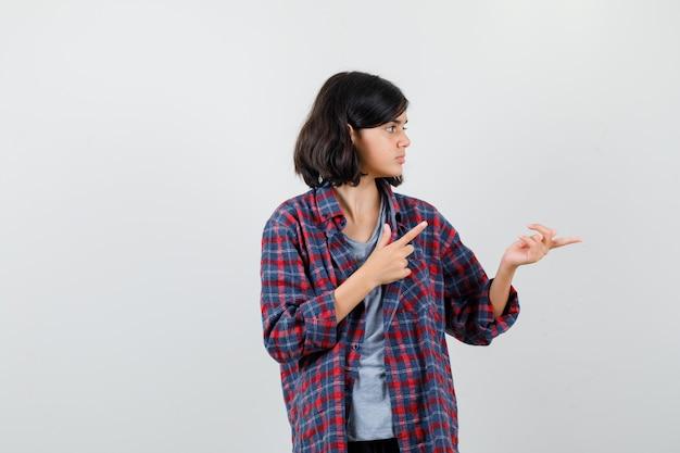 Teen girl in checkered shirt pointant sur le côté et vers le haut et à grave , vue de face.