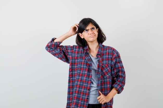 Teen girl in checkered shirt se grattant la tête et à la perplexité , vue de face.