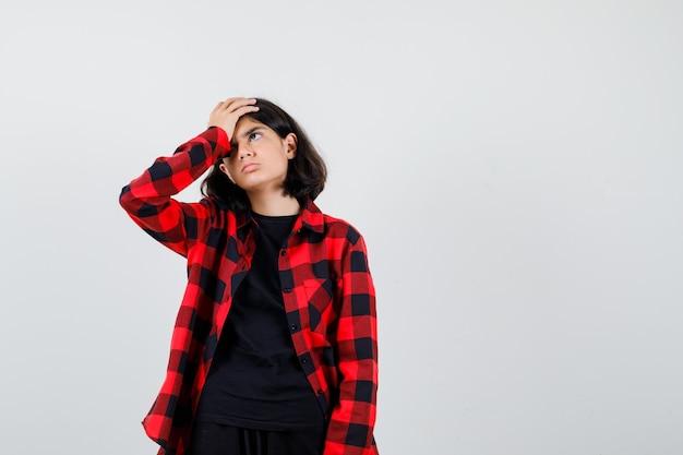 Teen girl in t-shirt, chemise à carreaux tenant la main sur le front et l'air fatigué, vue de face.