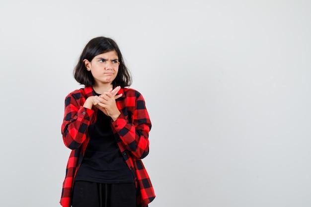 Teen girl in t-shirt, chemise à carreaux tenant les mains jointes et l'air sérieux, vue de face.