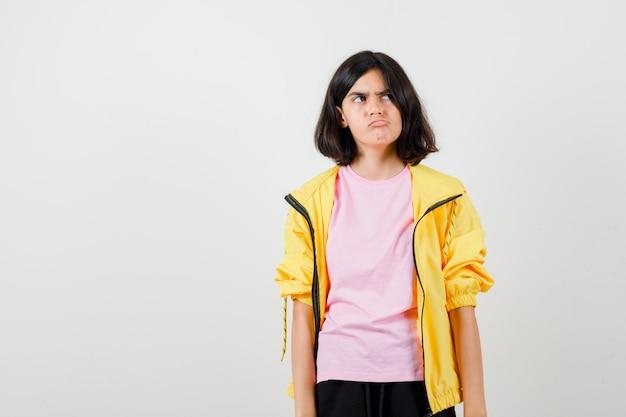 Teen girl in t-shirt, veste courbant la lèvre inférieure, regardant ailleurs et ayant l'air de s'ennuyer, vue de face.