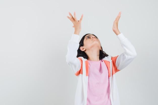 Teen girl levant ses mains avec paume ouverte en veste, chemise rose et à l'espoir
