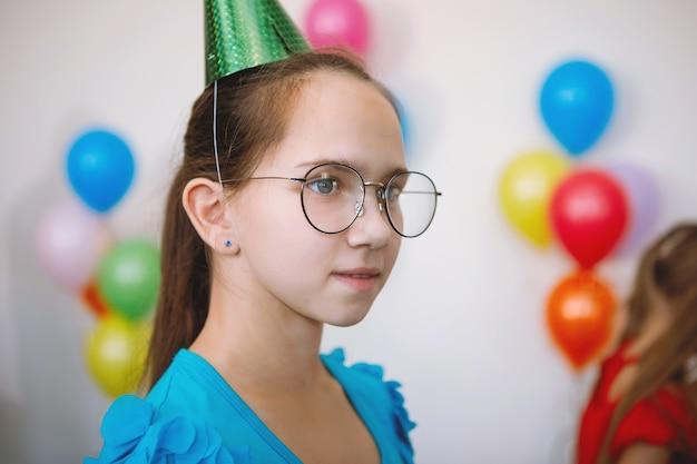 Teen girl à lunettes et chapeau de fête lors d'une fête d'anniversaire