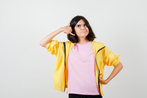 Teen girl montrant le geste du téléphone tout en posant en t-shirt, veste et à la recherche de bonheur. vue de face.