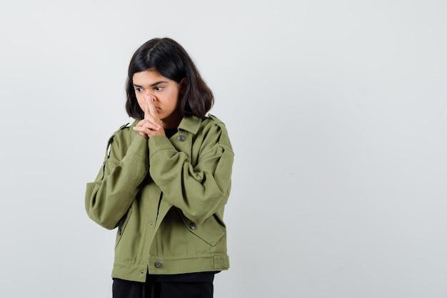 Teen girl pinçant le nez avec les doigts en t-shirt, veste verte et pensif , vue de face.