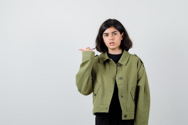 Teen girl pointant de côté avec le pouce en veste verte de l'armée et à la perplexité , vue de face.