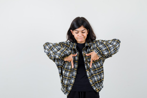 Teen girl pointant vers le bas en chemise décontractée et à la colère. vue de face.