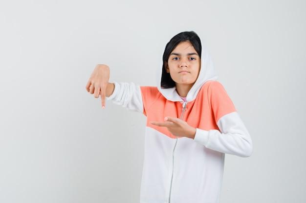 Teen girl pointant vers le bas en veste blanche et à la mécontentement