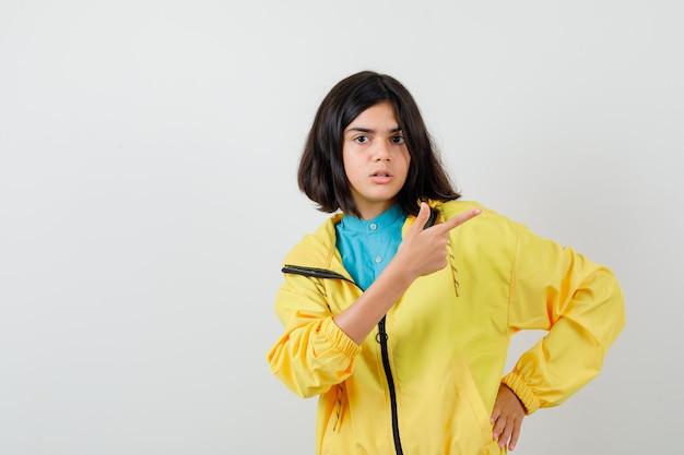 Teen girl pointant vers le coin supérieur droit en veste jaune et à la perplexité. vue de face.