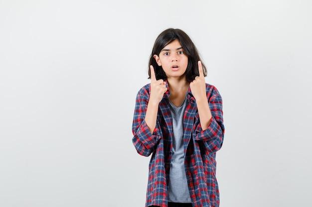 Teen girl pointant vers le haut en chemise à carreaux et à la surprise, vue de face.