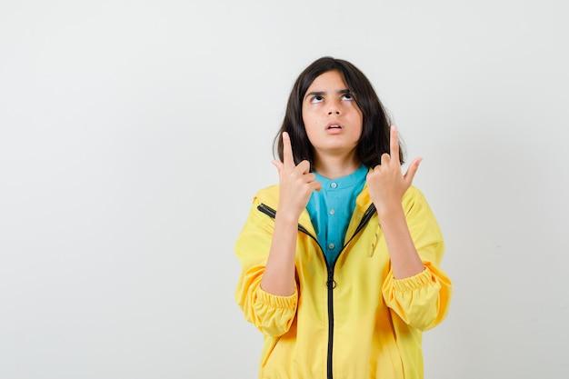 Teen Girl Pointant Vers Le Haut, Regardant Vers Le Haut En Veste Jaune Et à La Perplexité. Vue De Face. Photo gratuit