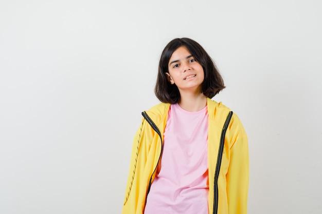 Teen girl posing debout en t-shirt, veste jaune et à la béatitude. vue de face.