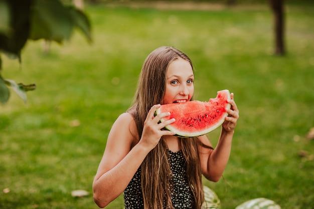 Teen girl posing avec tranche de pastèque dans le jardin avec espace de copie de récolte