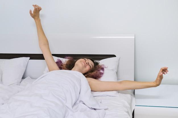 Teen girl se réveiller le matin allongé sur un oreiller dans son lit avec les bras ouverts
