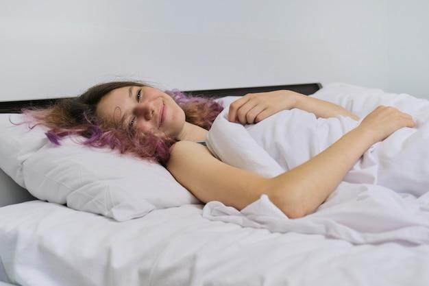 Teen girl se réveiller le matin allongé sur un oreiller dans son lit