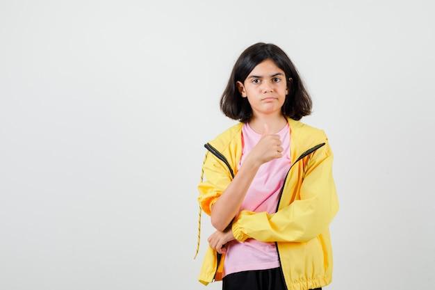 Teen girl showing thumb up en t-shirt, veste et à la colère. vue de face.