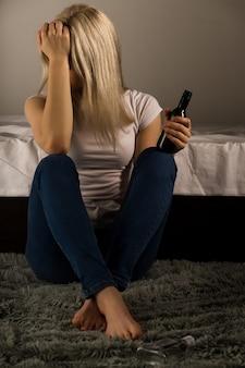 Teen girl souffrant d'une gueule de bois alors qu'il était assis sur le sol